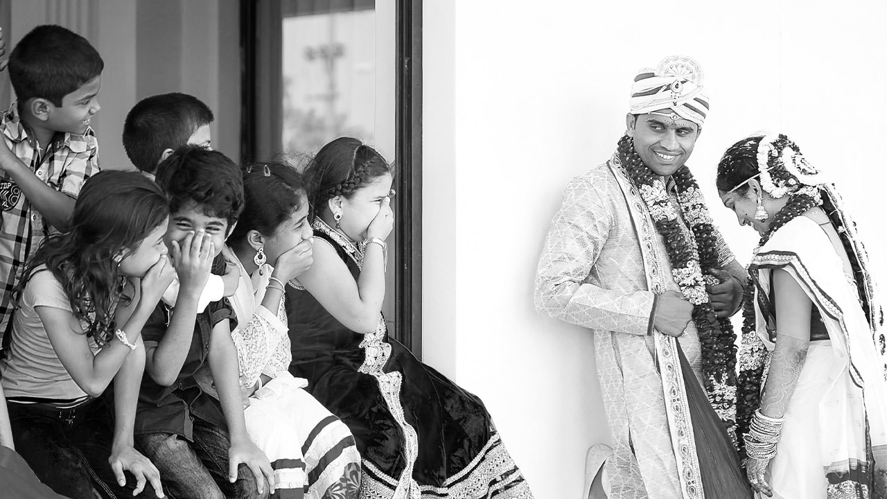 children laughing at a indian bride and groom posing